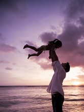 father lifting daughter up towards the sky